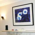 Framed blue floral artwork above fireplace