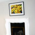 Framed floral artwork above fireplace